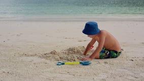 Ένα παιδί κάθεται στην παραλία κοντά στο νερό και σκάβει μια τρύπα με ένα φτυάρι φιλμ μικρού μήκους