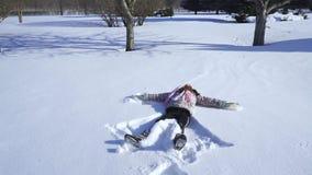 Ένα παιδί κάνει έναν άγγελο χιονιού απόθεμα βίντεο