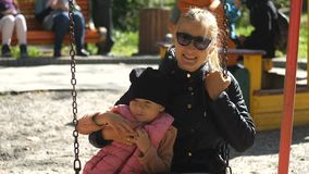 Ένα παιδί και η μητέρα του οδηγούν σε μια ταλάντευση στο πάρκο ηλιόλουστο ημερησίως φθινοπώρου Οικογενειακή ημέρα, γενέθλια, υπόλ απόθεμα βίντεο