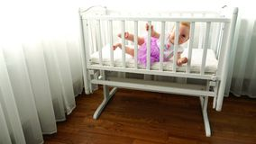 Ένα παιδί κλίνει στην πλευρά μιας άσπρης κούνιας παιδιών ` s στην κρεβατοκάμαρα απόθεμα βίντεο