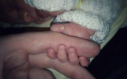 Ένα παιδί κρατά έναν μπαμπά από το δάχτυλό του στοκ εικόνες
