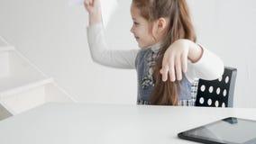 Ένα παιδί με μια ταμπλέτα και ένα βιβλίο Μια μαθήτρια μαθαίνει με ένα βιβλίο εγγράφου και ένα eBook απόθεμα βίντεο