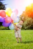 Ένα παιδί με τα ζωηρόχρωμα μπαλόνια Ευτυχές παιδί στα γενέθλιά του στο gre Στοκ εικόνα με δικαίωμα ελεύθερης χρήσης