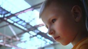 Ένα παιδί με τα πολύ λυπημένα μάτια βλέπει από κάποιο στον αερολιμένα, ένα πορτρέτο κινηματογραφήσεων σε πρώτο πλάνο ενός αγοριού απόθεμα βίντεο