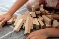 Ένα παιδί παίζει με τους ξύλινους φραγμούς παιχνιδιών Στοκ Εικόνες
