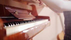 Ένα παιδί που ανοίγει μια κάλυψη πιάνων απόθεμα βίντεο