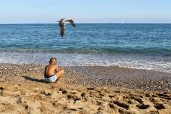 Ένα παιδί που παίζει βλέπει την ακτή στοκ εικόνα