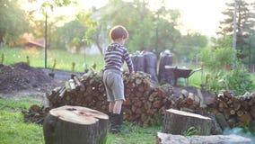 Ένα παιδί πυρών προσκόπων ρίχνει επάνω σε ένα κούτσουρο φιλμ μικρού μήκους
