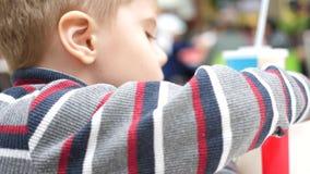 Ένα παιδί σε έναν καφέ γρήγορου φαγητού που τρώει τις τηγανισμένες πατάτες σε ένα πιάτο Στενός επάνω χεριών Φέτες των πατατών, πο φιλμ μικρού μήκους