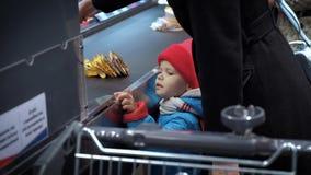 Ένα παιδί στέκεται κοντά στον έλεγχο υπεραγορών και εξετάζει τα αγαθά απόθεμα βίντεο
