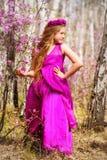Ένα παιδί στέκεται μεταξύ του ledum και της σημύδας σε ένα ρόδινα φόρεμα και ένα χαμόγελο στοκ φωτογραφίες