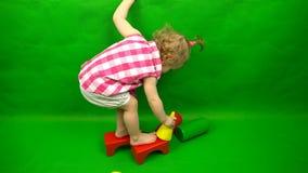 Ένα παιδί στέκεται με τα πόδια του στους κύβους ενός σχεδιαστή σε ένα πράσινο υπόβαθρο απόθεμα βίντεο