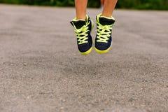 Ένα παιδί στα πάνινα παπούτσια καλαθοσφαίρισης πηδά επάνω Μόνο τα πόδια του στο λυκίσκο κλείνουν στοκ εικόνες