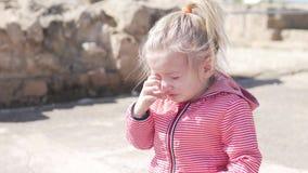 Το μικρό κορίτσι φωνάζει Ένα παιδί στην οδό σε ένα σακάκι βρυχείται απόθεμα βίντεο