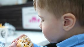 Ένα παιδί τρώει ένα κουλούρι με cutlet και το τυρί σε ένα εστιατόριο γρήγορου φαγητού απόθεμα βίντεο