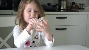 Ένα παιδί τρώει το μέλι με ένα κουτάλι από ένα πλαστικό βάζο απόθεμα βίντεο