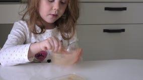 Ένα παιδί τρώει το μέλι με ένα κουτάλι από ένα πλαστικό βάζο φιλμ μικρού μήκους
