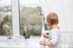 Ένα παιδί φαίνεται έξω το παράθυρο Στοκ Εικόνα