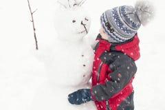 Ένα παιδί sculpts ένας χιονάνθρωπος το χειμώνα στην οδό, ένα αγόρι σε ένα κόκκινο συνολικά Στοκ Φωτογραφίες