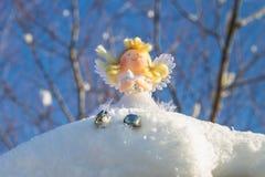Ένα παιχνίδι αγγέλου νεράιδων κάθεται στο χιόνι απομονωμένο λευκό παιχνιδιών σφαιρών Χριστουγέννων ανασκόπησης γυαλί Στοκ φωτογραφία με δικαίωμα ελεύθερης χρήσης