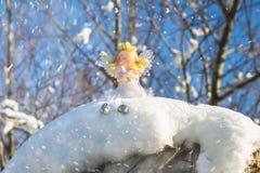 Ένα παιχνίδι αγγέλου νεράιδων κάθεται στο χιόνι απομονωμένο λευκό παιχνιδιών σφαιρών Χριστουγέννων ανασκόπησης γυαλί Στοκ εικόνα με δικαίωμα ελεύθερης χρήσης
