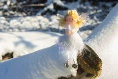 Ένα παιχνίδι αγγέλου νεράιδων κάθεται στο χιόνι απομονωμένο λευκό παιχνιδιών σφαιρών Χριστουγέννων ανασκόπησης γυαλί Στοκ Εικόνες