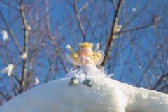 Ένα παιχνίδι αγγέλου νεράιδων κάθεται στο χιόνι απομονωμένο λευκό παιχνιδιών σφαιρών Χριστουγέννων ανασκόπησης γυαλί Στοκ φωτογραφίες με δικαίωμα ελεύθερης χρήσης