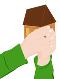 Ένα παιδί κρατά ένα σπίτι Στοκ Εικόνες