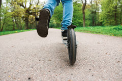 Ένα παιδί οδηγά το μηχανικό δίκυκλό της στο πάρκο Στοκ Εικόνες