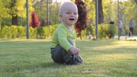 Ένα παιδί παίζει στο πάρκο στη χλόη Αγόρι, ξανθό, μωρό, πρώτα βήματα απόθεμα βίντεο