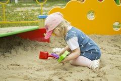 Ένα παιδί που παίζει στην κινηματογράφηση σε πρώτο πλάνο Sandbox στοκ φωτογραφία