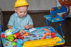 Ένα παιδί σε ένα κράνος κατασκευής με τα εργαλεία παιχνιδιών επισκευάζει τα παιχνίδια στοκ φωτογραφίες με δικαίωμα ελεύθερης χρήσης