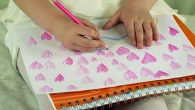 Ένα παιδί σύρει με τα χρωματισμένα μολύβια πολλά ζωηρόχρωμα καρδιές και ουράνια τόξα απόθεμα βίντεο