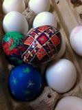 Ένα παιδί ` s Πάσχα Pysanka που στηρίζεται πάνω από ένα χαρτοκιβώτιο αυγών Στοκ Εικόνες