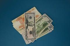 ένα πακέτο των ρωσικών ρουβλιών και των δολαρίων δύο wads των χρημάτων σε ένα μπλε υπόβαθρο πλούτος της ευκαιρίας επιτυχία στοκ φωτογραφία