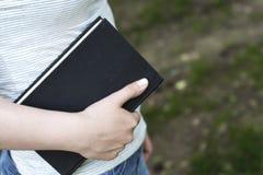 Ένα παλαιό βιβλίο κατά την πλάγια όψη χεριών μιας γυναίκας, διάστημα αντιγράφων, έννοια στοκ εικόνα