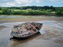 Ένα παλαιό ξύλινο αλιευτικό σκάφος βάζει στην πλευρά του at low tide στοκ εικόνες με δικαίωμα ελεύθερης χρήσης