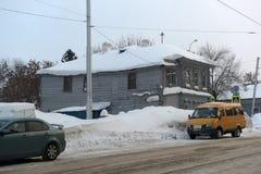 Ένα παλαιό ξύλινο σπίτι στην οδό πόλεων το χειμώνα Στοκ Φωτογραφίες