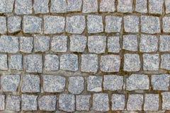 Ένα παλαιό πεζοδρόμιο stoneblock με τους τετραγωνικούς φραγμούς γρανίτη Στοκ Φωτογραφίες