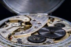 Ένα παλαιό ρολόι σε έναν σκοτεινό πίνακα Μηχανισμός χρονομέτρων που βλέπει διευρυμένος Στοκ Εικόνα