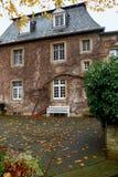 Ένα παλαιό φέουδο στο δασικό παλαιό φέουδο φθινοπώρου και ζωηρόχρωμη ανάπτυξη κισσών στους τοίχους Στοκ Φωτογραφίες