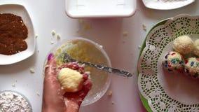 Ένα παντρεμένο ζευγάρι προετοιμάζει τα γλυκά από το συμπυκνωμένο γάλα, τα ξέσματα καρύδων και τα αμύγδαλα απόθεμα βίντεο
