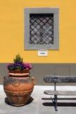 Ένα παράθυρο, δοχείο με τα λουλούδια και μισός πάγκος στο μικρό μέρος στην Τοσκάνη Στοκ Εικόνες