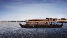 Ένα παραδοσιακό πλωτό σπίτι δένεται στις ακτές μιας λίμνης αλιείας στα τέλματα του Κεράλα, Ινδία - Εικόνα στοκ εικόνα