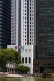 Ένα παραδοσιακό bumboat στον ποταμό της Σιγκαπούρης με τα σύγχρονα κτίρια γραφείων στο υπόβαθρο Στοκ Φωτογραφίες