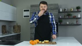 Ένα παχύ άτομο με μια γενειάδα κόβει τα πορτοκάλια σε έναν τέμνοντα πίνακα Ο παχουλός τύπος δοκιμάζει τα juicy φρούτα Το πρόσωπο  απόθεμα βίντεο