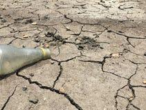 Ένα παλαιό μπουκάλι νερό στο ξηρό και ραγισμένο έδαφος κάνει την παγκόσμια αύξηση της θερμοκρασίας λόγω του φαινομένου του θερμοκ στοκ εικόνες με δικαίωμα ελεύθερης χρήσης