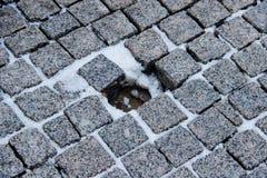 Ένα παλαιό πεζοδρόμιο stoneblock με μια τρύπα σε ισχύ μιας πέτρας Στοκ Εικόνες