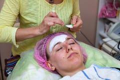 Ένα πεπειραμένο cosmetologist εφαρμόζει μια μάσκα της άσπρης κρέμας στο πρόσωπο ενός νέου κοριτσιού που βρίσκεται στον καναπέ κατ στοκ φωτογραφίες με δικαίωμα ελεύθερης χρήσης