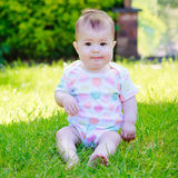 Ένα περίεργο μωρό σε μια συνεδρίαση φανέλλων σε μια χλόη Στοκ φωτογραφίες με δικαίωμα ελεύθερης χρήσης